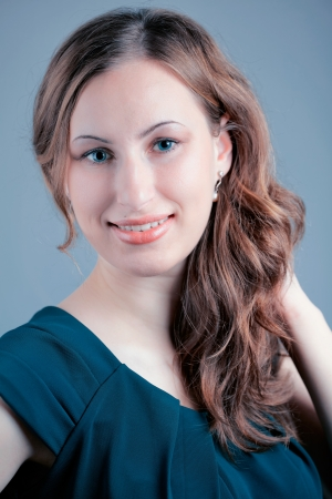 Studio portrait of a beautiful 20 year old redhead woman against blue background. Stock Photo - 16947179
