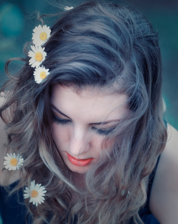 Portrait of a beautiful 20 year old woman with long hair and flowers in her hair. photo