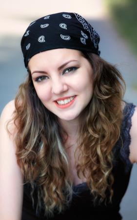 Porträt einer schönen 20 Jahre alten Frau im Freien ein Kopftuch trägt, wie Rocker.