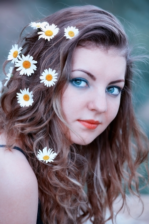 Portrait of young caucasian woman with flowers in her hair outdoor. photo