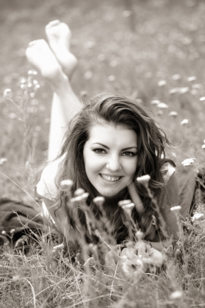 20 year old: 20 year old woman lying down on the grass, black and white image.