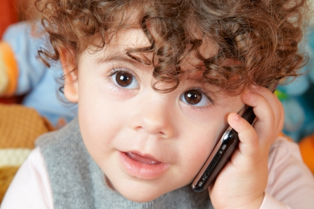 Two year old girl with curly hair talking on phone. Stock Photo
