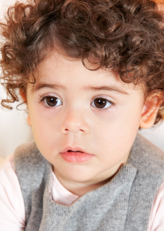 two year old: Two year old baby girl with curly hair portrait.