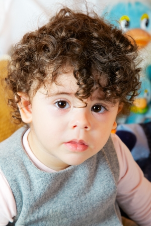 two year old: Two year old girl with curly hair portrait, studio shot.