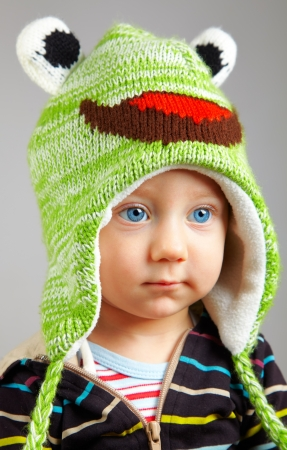Portrait of a cute little adorable child with funny green hat over gray background photo