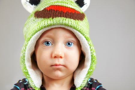 Portrait of a cute little adorable child with funny green hat over gray background Stock Photo - 17623277