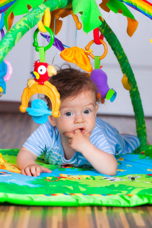 tummy time: Portrait of a happy 6 months old baby boy at tummy time on the play gym. Stock Photo