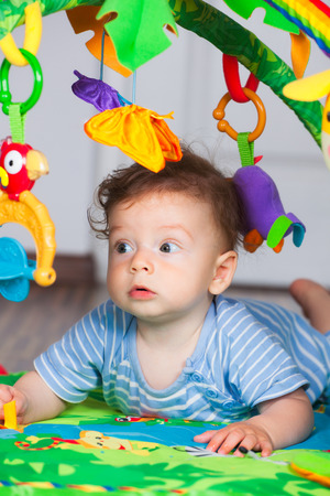 7 months: Portrait of 7 months old baby boy playing with toys. Stock Photo
