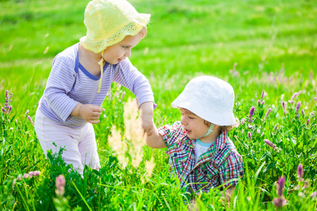 socialise: Portrait of 1 year old baby boy and baby girl outdoor on a meadow. Stock Photo