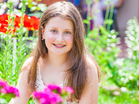 pretty dress: Portrait of a 10 year old girl enjoying the flower garden at home.