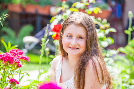 10 year old: Portrait of a 10 year old girl enjoying the flower garden at home.