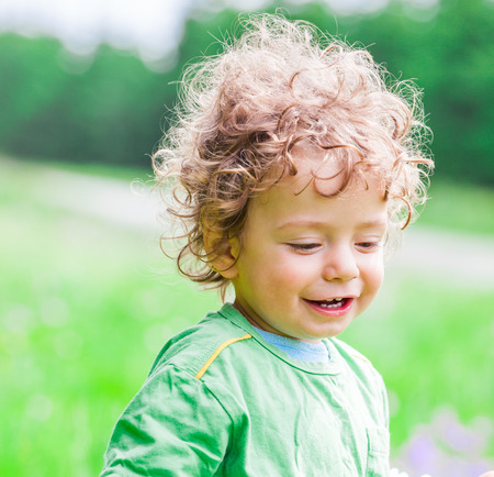 boy long hair: Portrait of 1 year old baby boy having fun on a mountain meadow. Stock Photo
