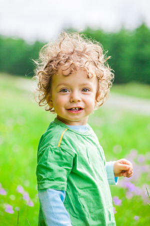 Portrait of 1 year old baby boy having fun on a mountain meadow. Stock Photo