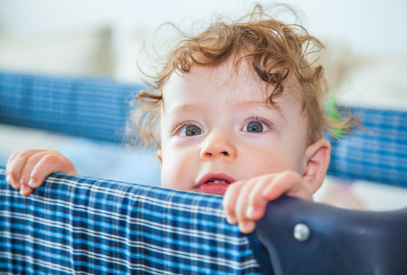 playpen: Portrait of a 9 months old baby boy peeking from his
