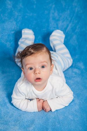 blue blanket: Portrait of an adorable baby boy on a blue blanket.