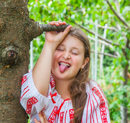 tongues: Portrait of a 10 year old girl wearing a Romanian traditional blouse.
