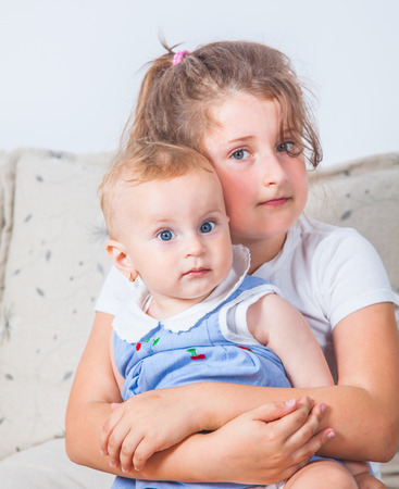 Big sister holding her 1 year old baby sister. photo