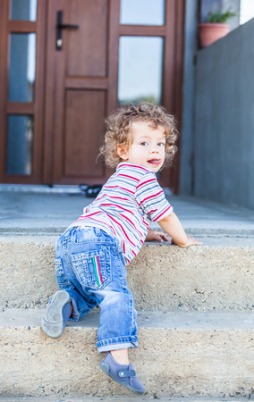 curly hair child: Portrait of 1 year old baby boy climbing down the stairs.