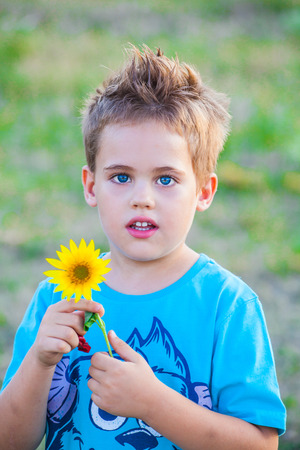 5 year old: Portrait of a 5 year old boy outdoor, with sunflower in his hand.