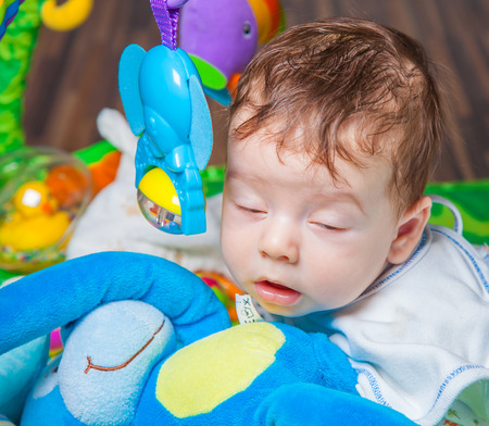 playmat: Baby boy falling asleep while playing on the playmat.
