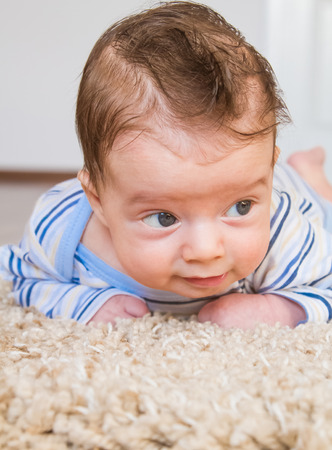 2 months: 2 months old baby boy enjoying tummy time on the carpet at home. Stock Photo