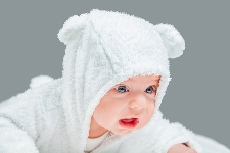 2 months: 2 months old baby boy wearing bunny suit and crying. Stock Photo