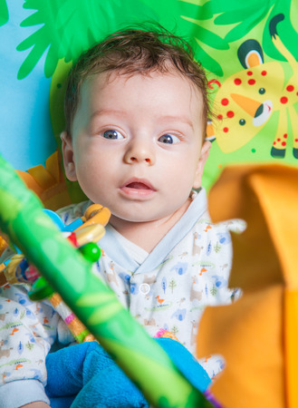 playmat: 3 months old baby boy playing and learning on the playmat.