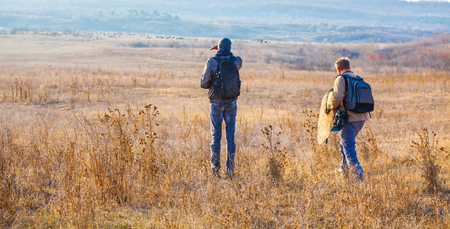 documenting: Biologists walking through the field at sunset nearby Stanca village, Iasi, Romania.