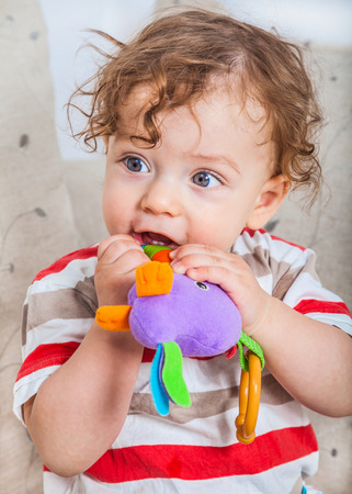 11: 11 months old baby boy chewing on a toy on the sofa at home. Stock Photo