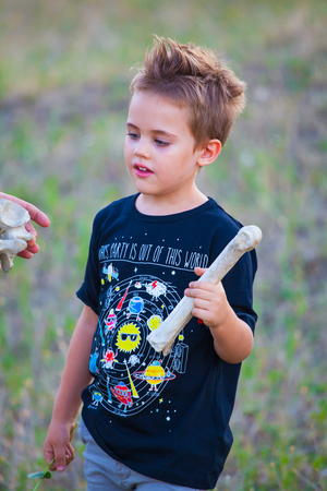 5 year old: Portrait of a 5 year old boy outdoor checking an animal bone.