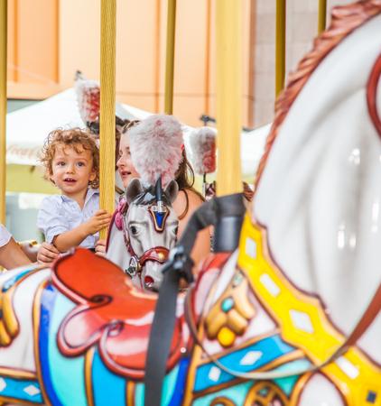 Baby boy having fun in a carousel. photo