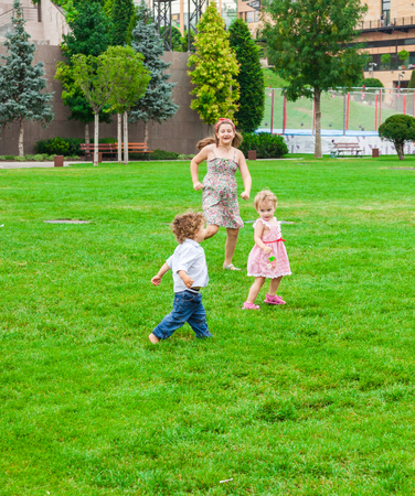 Baby boy and baby girl playing with their older sister in the park. photo