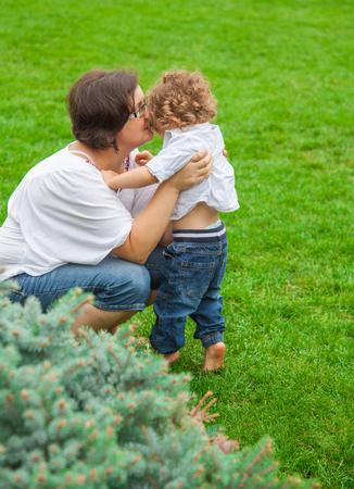 liesure: Woman hugging baby boy in the park. Stock Photo