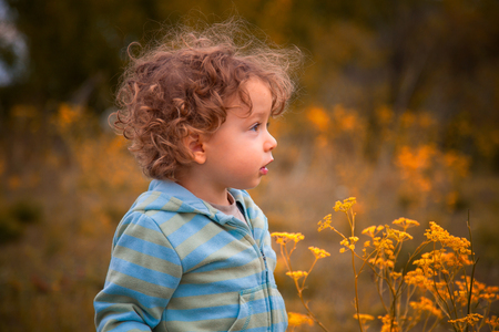 boy long hair: 1 year old baby boy walking through the countryside.