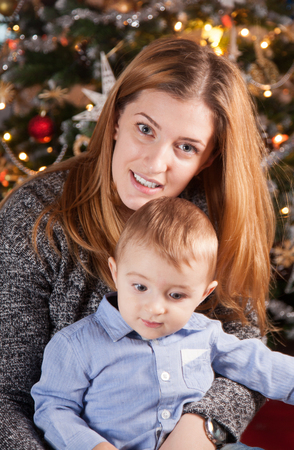 baby near christmas tree: 1 year old baby boy in his mothers arms, near the Christmas tree.