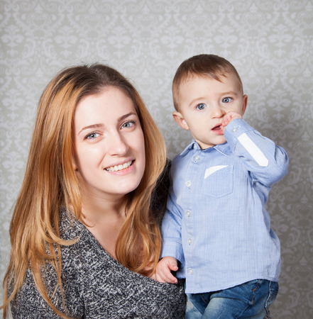 boy 12 year old: 1 year old baby boy in his mothers arms, studio portrait.