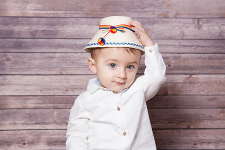 romanian: Portrait of a 1 year old baby boy wearing a Romanian traditional hat.