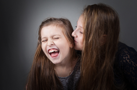 10 year old: Portrait of8 and 10 year old sisters, studio shot.