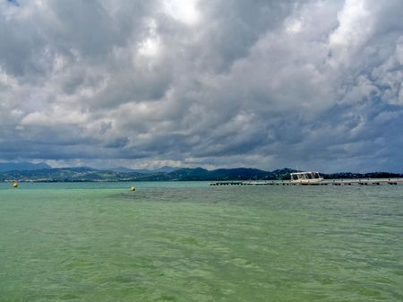 stormy waters: stormy clouds over tropical green waters
