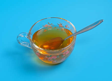 glass cup with green tea and spoon