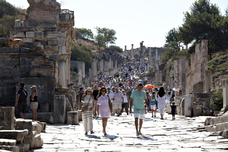Izmir, Turkey - September, 25th 2011: Tourists walking on Kuretes street. The street is one of the main streets of Ephesus, 210m long, that connects the Magnesia Gate to the Koresos Gate. This path erlier known as Cotege Path of Artemis.