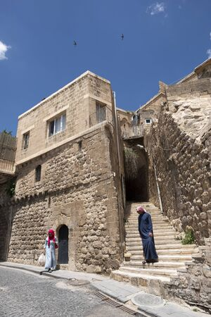 Mardin, Turkey: May 18, 2018: Peopla in traditional clothes in Mardin, Turkey on May 18, 2018.