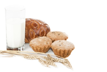 Glass of milk, biscuits, cake and three ears of wheat on a white background.  photo