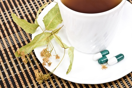 A cup of tea, dry lime flowers and tablets. photo