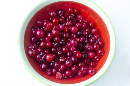 Raw Red Cranberries in a Bowl on the white background Standard-Bild - 121336987