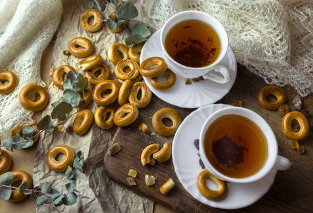 Russian traditional sweets dry bakery bagels and 2 white cups of tea Standard-Bild - 121337421