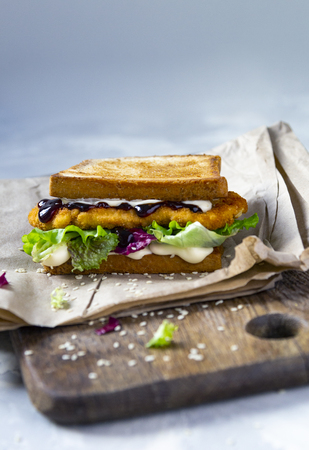 Katsu Sando at wooden desk - food trend japanese sandwich with chicken cutlet, cabbage and tonkatsu sauce. Japanese cuisine Standard-Bild - 121337425