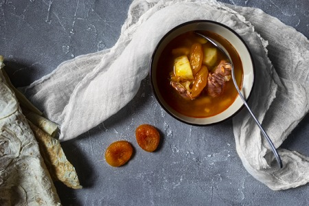 Armenian cuisine. Yajni - beef soup with dried apricot Standard-Bild - 121337523