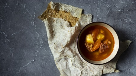 Armenian cuisine. Lavash bread and Yajni - beef soup with dried apricot Standard-Bild - 121337525
