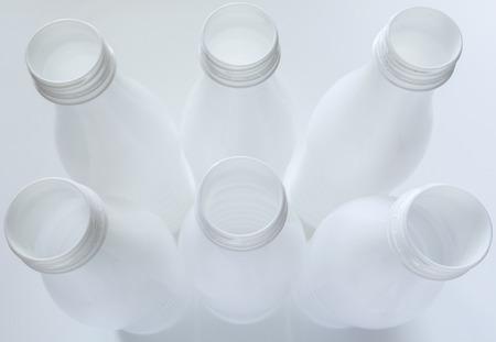 Empty white plastic milk bottles on White background